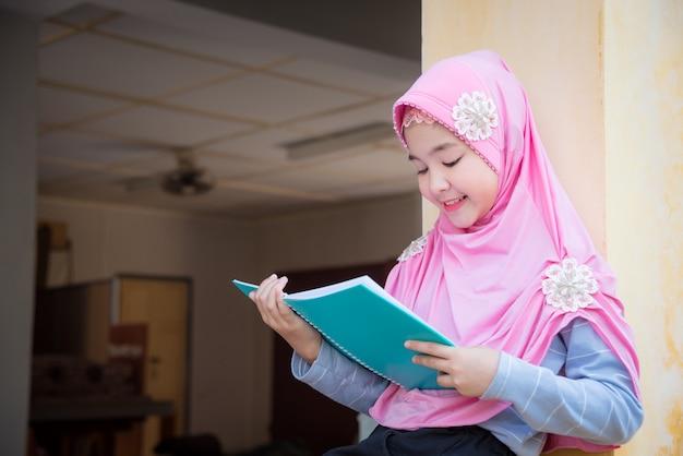 Livre de lecture jolie fille musulmane et sourires. Photo Premium