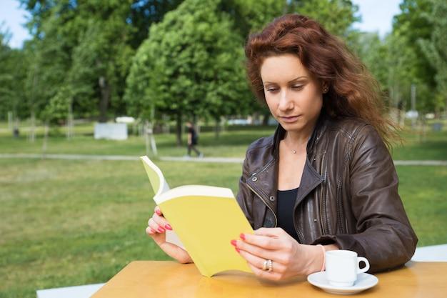 Livre de lecture jolie jeune femme au café du collège Photo gratuit