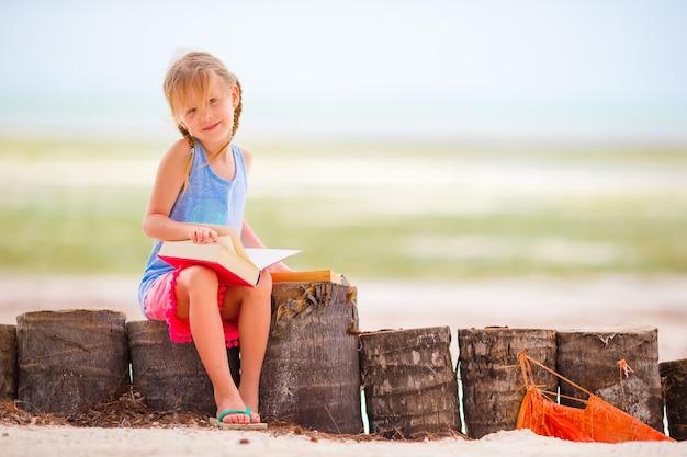 Livre de lecture de petite fille adorable au cours de la plage blanche tropicale Photo Premium