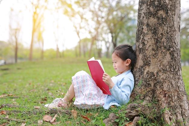Livre de lecture de petite fille en été parc en plein air s'appuyer contre le tronc d'arbre dans le jardin d'été. Photo Premium