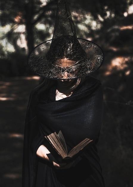 Livre de lecture sorcière en pleine forêt Photo gratuit