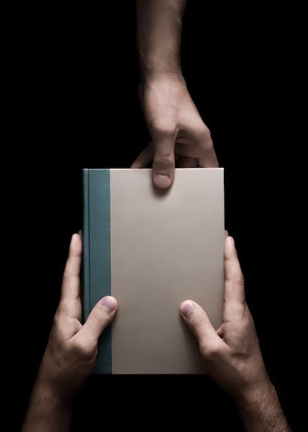 Livre En Mains Mâles Sur Fond Noir Photo Premium