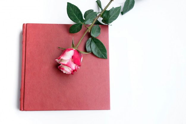 Livre De Mariage Recouvert De Cuir Rouge Ou Album De Mariage Se Trouvent Sur Fond Blanc, Une Rose Se Trouve Sur Le Livre De Mariage. Photo Premium