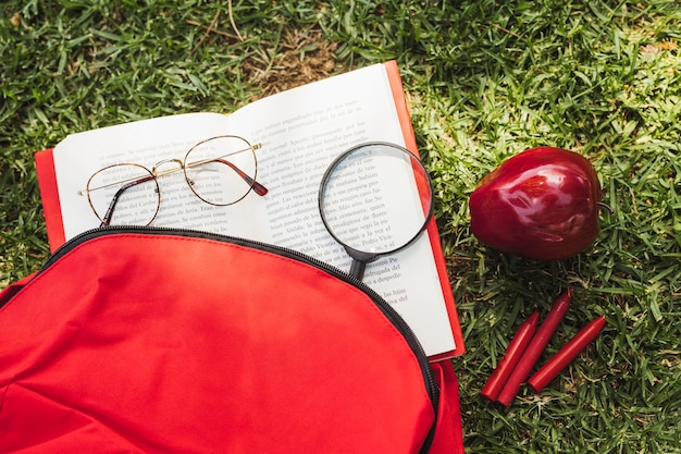 Livre Avec Outils Optiques Près Du Sac à Dos Et De La Pomme Photo gratuit