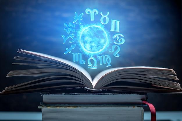 Livre ouvert sur l'astrologie. le globe magique rougeoyant avec des signes du zodiaque à la lumière bleue Photo Premium