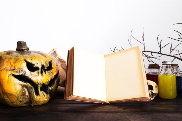 Livre ouvert et citrouille effrayante sur table Photo gratuit