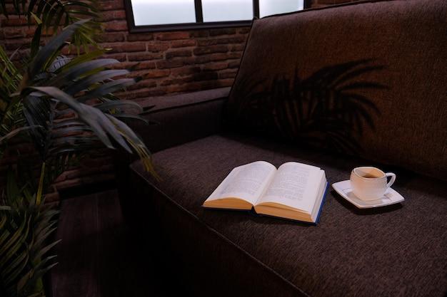 Livre ouvert et éclairage cbright studio à l'intérieur de la pièce. film light.ap de café sur le canapé. intérieur sombre. Photo Premium