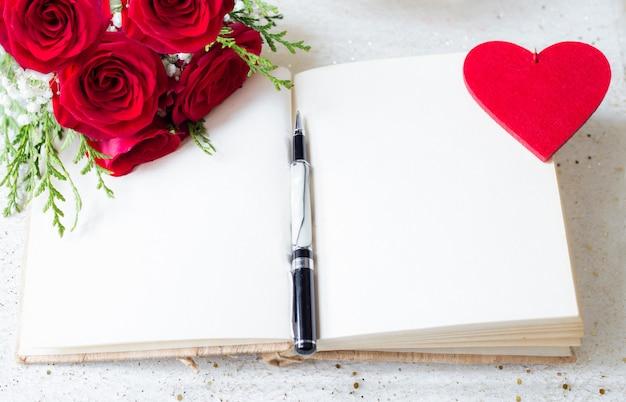 Livre ouvert avec des pages blanches et stylo sur et des roses rouges et fond de coeur senti Photo Premium