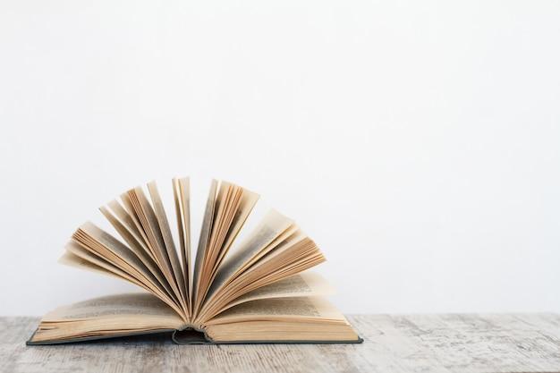 Livre ouvert sur une surface en bois dans le contexte d'un mur blanc Photo Premium