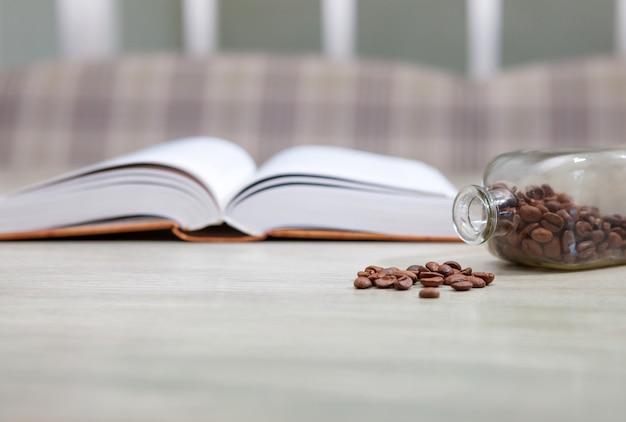 Un livre ouvert sur une table blanche et une bouteille de grains de café Photo Premium