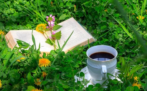 Livre ouvert et une tasse de café chaud dans une prairie verte en été ou au matin de printemps Photo Premium