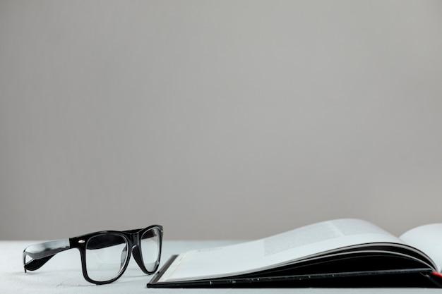 Livre ouvert vue de face avec des lunettes Photo gratuit