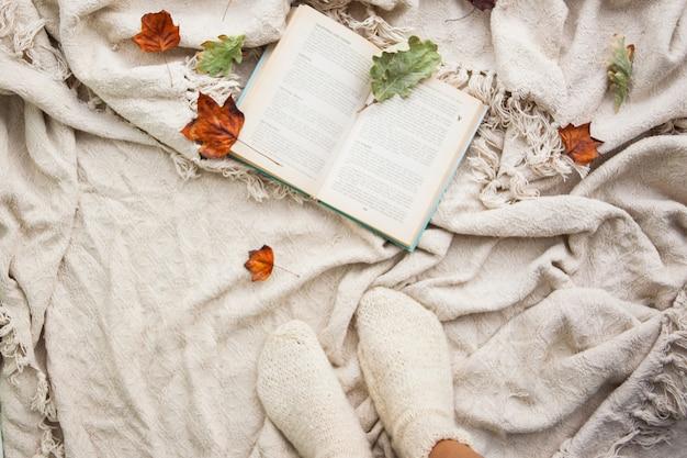Livre repose sur un plaid en laine beige. feuilles tombées et jambes tombées avec chaussettes en laine blanche Photo Premium