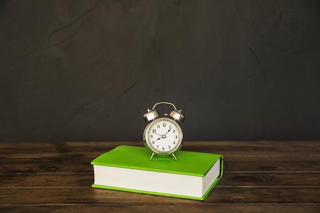 Livre Sur Table Avec Réveil Photo gratuit