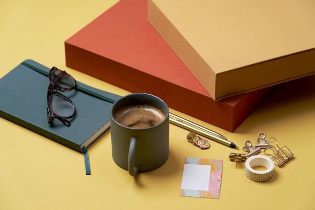 Livre, Tasse à Café, Lunettes De Lecture, Stylo Et Crayons Sur Jaune. Photo Premium