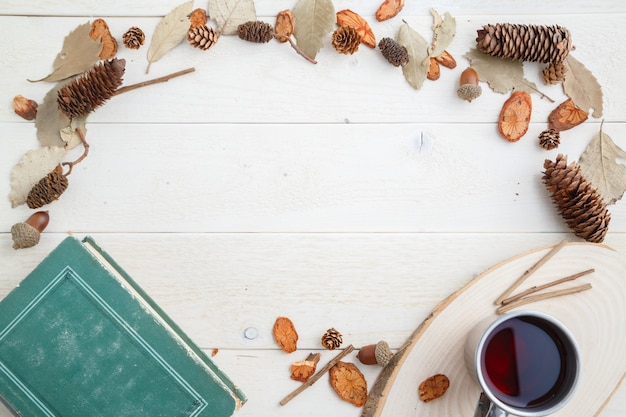 Livre vintage et boire dans une tasse rétro sur fond en bois. vue de dessus Photo Premium