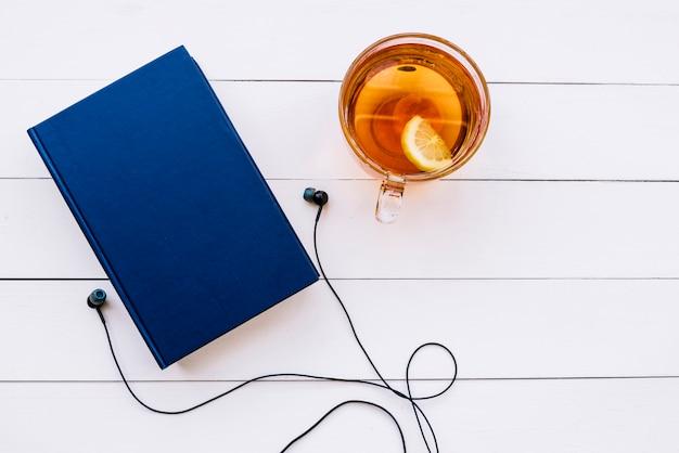 Livre vue de dessus avec du thé et des écouteurs Photo gratuit