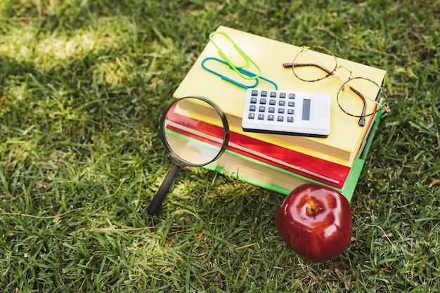 Livres Avec Instruments Optiques, Calculatrice Et Pomme Sur L'herbe Photo gratuit