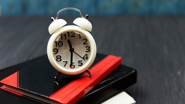 Livres et réveil regardent blanc sur un fond bleu en bois Photo Premium
