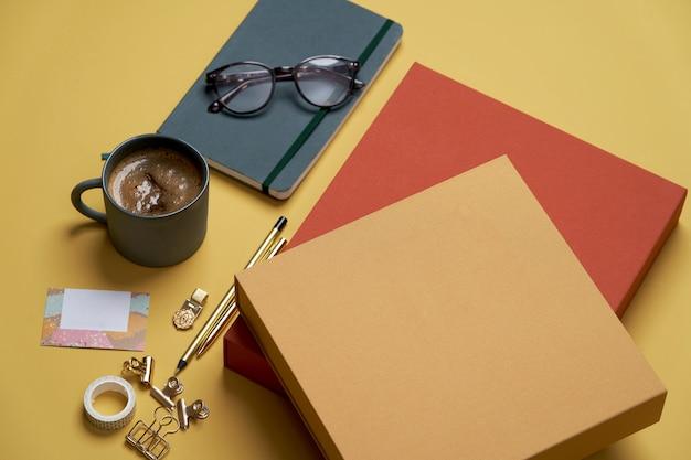 Livres, Tasse à Café, Lunettes De Lecture, Stylo Et Crayons Sur Jaune. Photo Premium