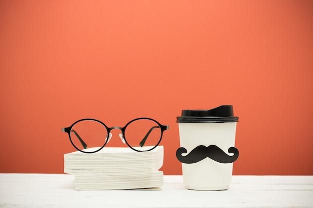 Livres, verres et coupe avec moustache sur une table en bois sur fond vintage orange Photo Premium