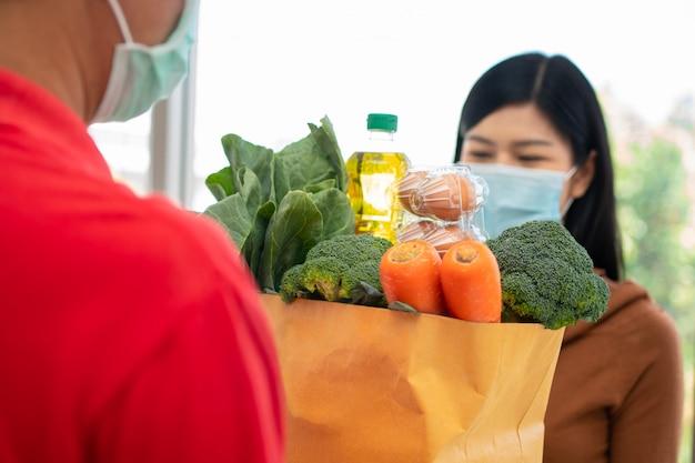 Livreur Asiatique De Supermarché Portant Un Masque Facial Et Tenant Un Sac De Nourriture Fraîche Pour Donner Aux Clients à La Maison. Photo Premium