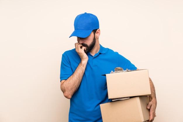 Livreur avec barbe sur mur isolé ayant des doutes Photo Premium
