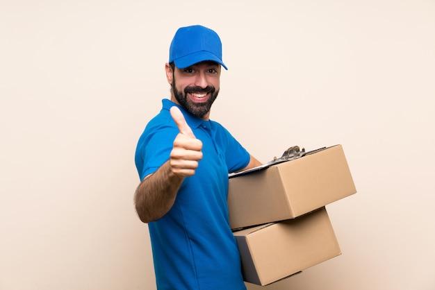 Livreur avec barbe sur un mur isolé avec le pouce levé parce que quelque chose de bien s'est passé Photo Premium