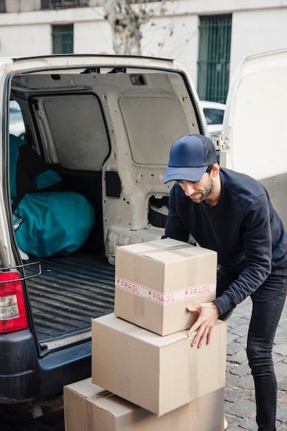 Livreur avec des boîtes en carton près du véhicule Photo gratuit