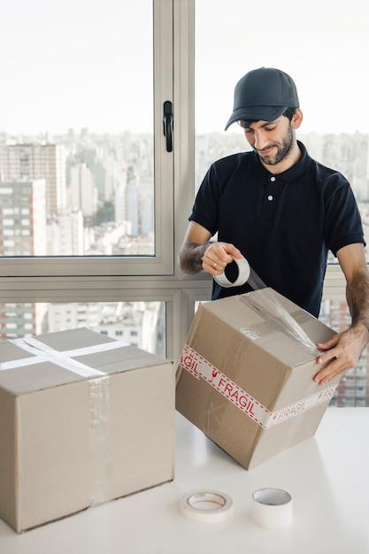 Livreur d'emballage colis avec du ruban de violoncelle Photo gratuit