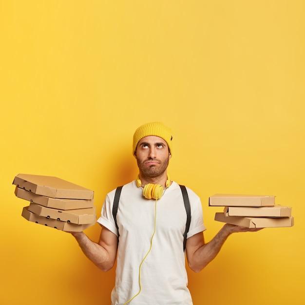 Livreur Fatigué Avec Des Boîtes à Pizza Photo gratuit