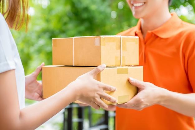 Livreur livrant une boîte à colis à une cliente Photo Premium