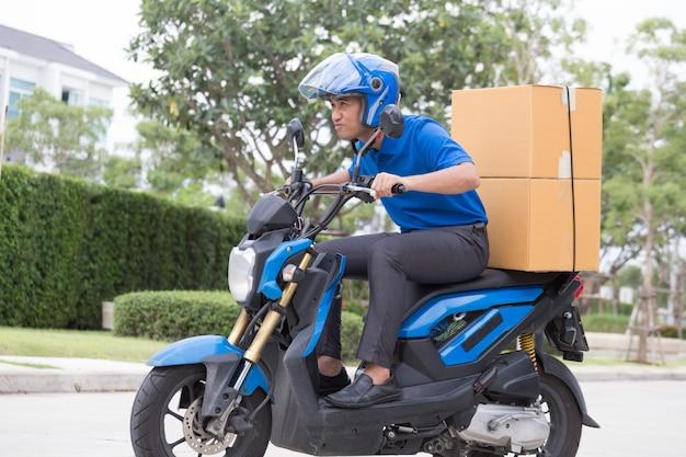 Livreur à moto avec coffre à colis conduisant au jeûne en hâte Photo Premium