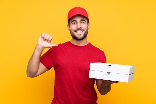 Livreur De Pizza Avec Uniforme De Travail Ramasser Des Boîtes à Pizza Sur Jaune Isolé Fier Et Satisfait De Lui-même Photo Premium