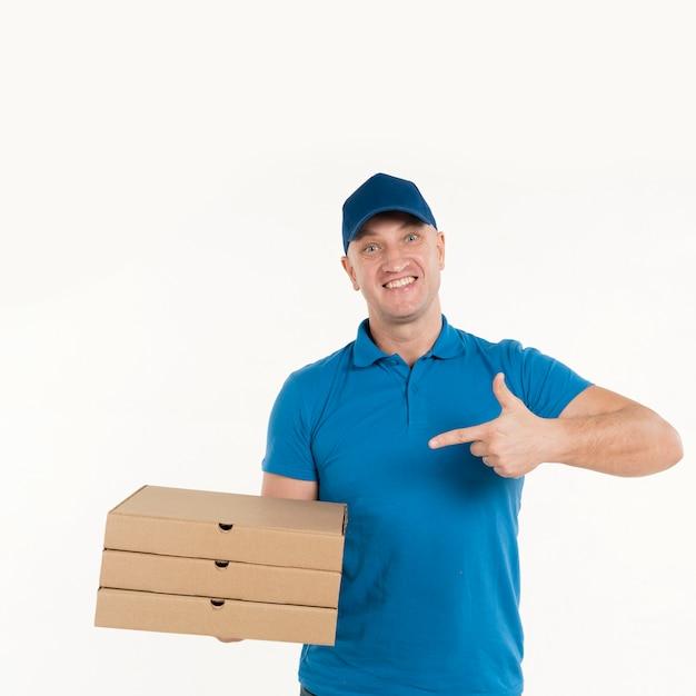 Livreur pointant sur des boîtes à pizza Photo gratuit