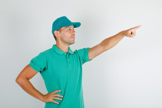Livreur Pointant Quelque Chose Avec La Main Sur La Taille En T-shirt Vert Avec Casquette Photo gratuit