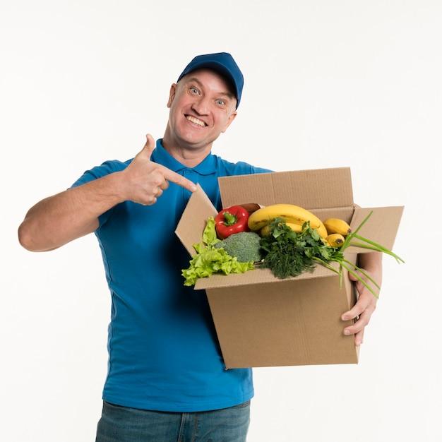 Livreur pointant vers la boîte d'épicerie Photo gratuit