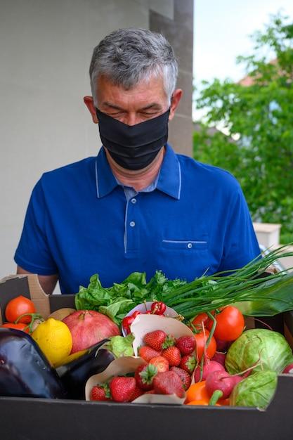 Livreur Portant Un Masque Facial Et Tenant Une Boîte De Légumes Photo gratuit