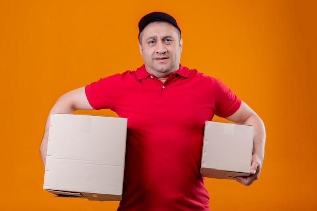 Livreur Portant L'uniforme Rouge Et Une Casquette Tenant Des Boîtes En Carton à Debout Surmené Et Fatigué Photo gratuit