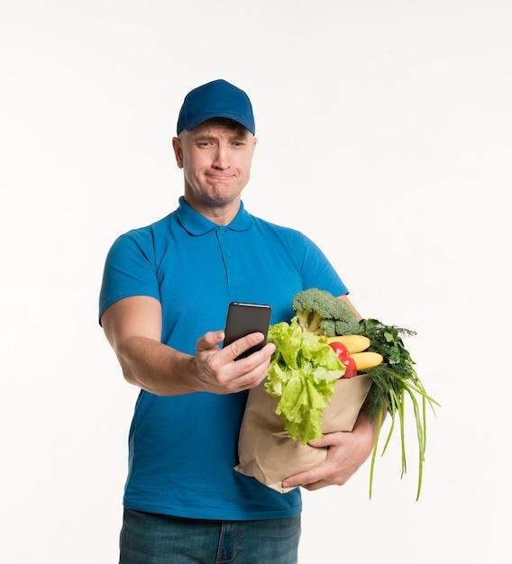 Livreur regardant smartphone tout en tenant le sac d'épicerie Photo gratuit