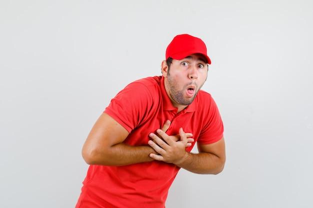 Livreur Se Sentir Nauséeux Avec Les Mains Sur La Poitrine En T-shirt Rouge Photo gratuit