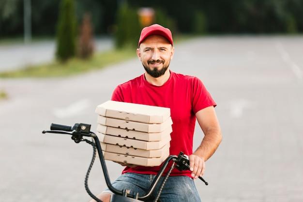 Livreur Smiley Tir Moyen Tenant Des Boîtes à Pizza Photo gratuit