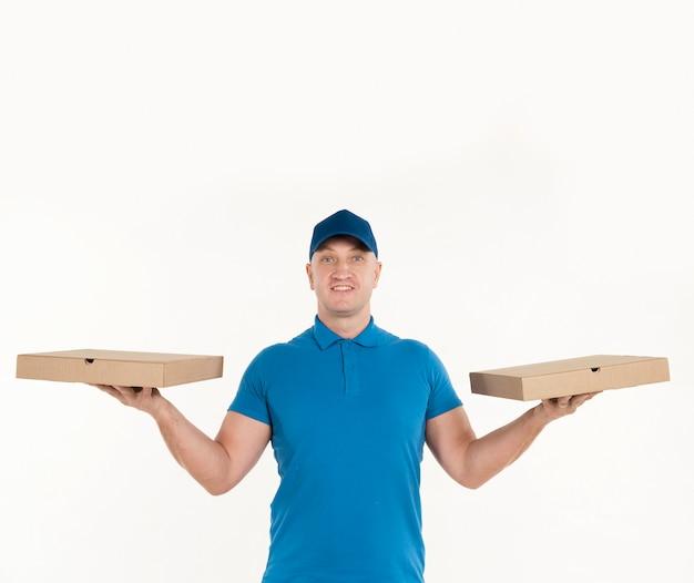 Livreur tenant des boîtes à pizza dans chaque main Photo gratuit