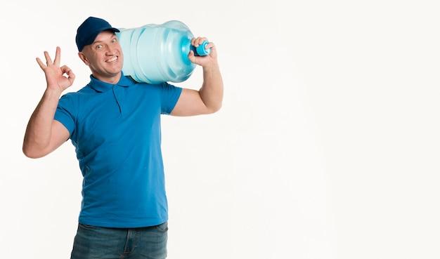 Livreur Tenant Une Bouteille D'eau Et Faisant Signe Ok Photo gratuit