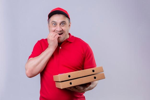 Livreur En Uniforme Rouge Et Cap Tenant Des Boîtes à Pizza à La Stress Et Nerveux Avec La Main Sur La Bouche Se Ronger Les Ongles Photo gratuit