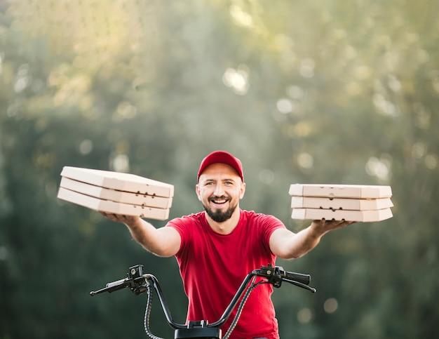 Livreur vue de face tenant des boîtes à pizza Photo gratuit