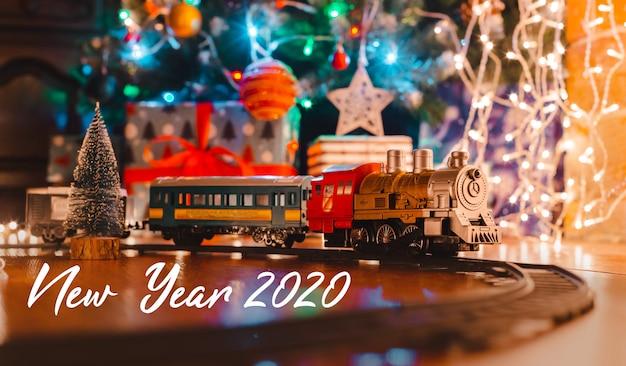 Locomotive à vapeur vintage jouet sur le sol sous un arbre de noël décoré sur un fond de guirlande de lumières bokeh. Photo Premium