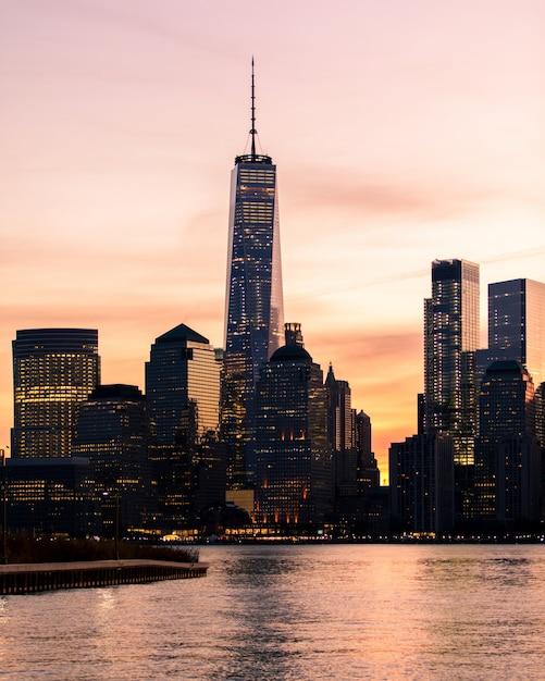 Lointain Tir Vertical Du Bâtiment Du World Trade Center à New York Pendant Le Coucher Du Soleil Photo gratuit