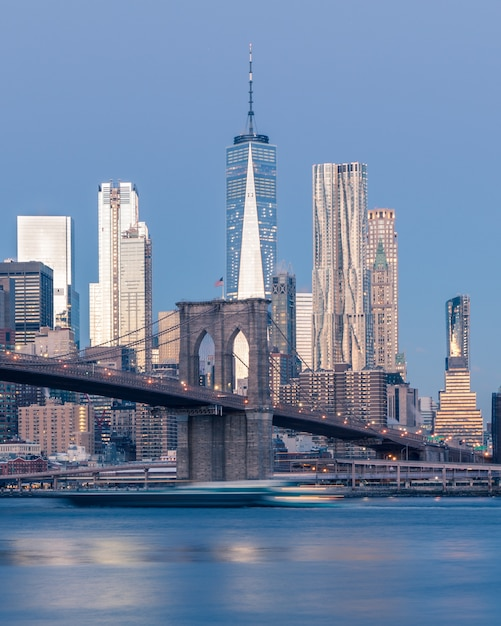 Lointain Tir Vertical Du Pont De Brooklyn Sur Le Plan D'eau Près De Gratte-ciel à New York Photo gratuit