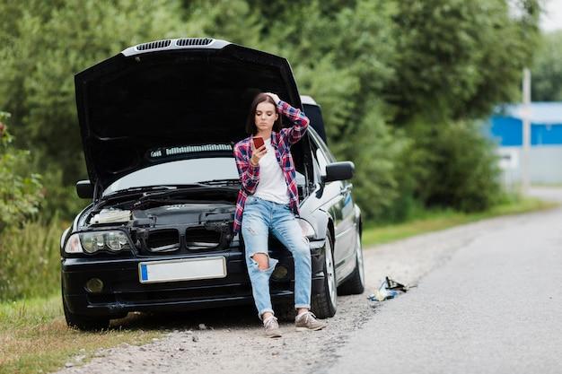 Long coup de femme assise sur la voiture Photo gratuit